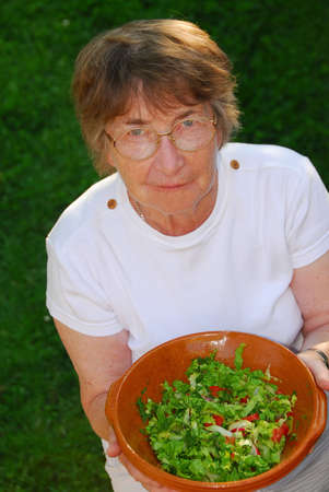 Happy senior woman with bowl of salad in her hands Stock Photo - 428709