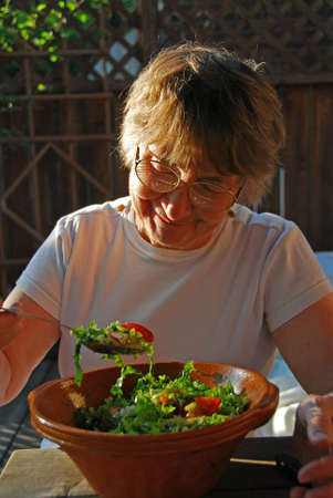 Happy senior woman in front of a bowl with garden salad photo