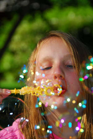 girl blowing: Young girl blowing soap bubbles
