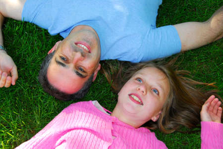 Happy family lying in green summer grass, father and child Stock Photo