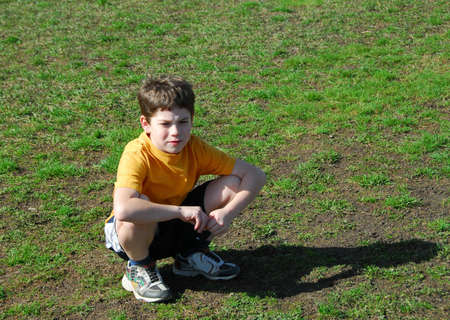 unhappiness: Little boy sitting upset on a soccer field after losing a game
