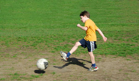 Young boy kicking soccer ball Stock Photo - 430224