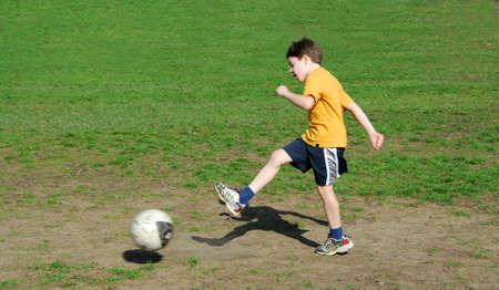 Young boy kicking soccer ball Stock Photo - 430224