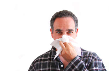Man with a flu blowing his nose photo