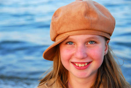 Cute preteen girl smiling wearing suede hat, blue water background photo