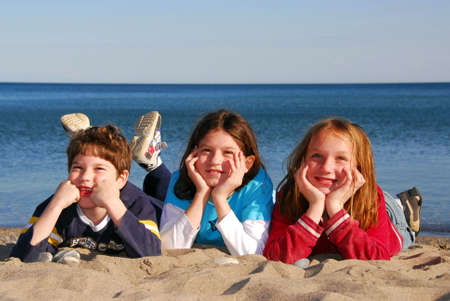 Three children lying on a beach laughing