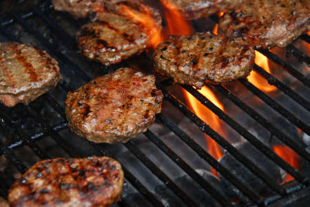 Hamburgers cooking on barbeque grill with flames Stock Photo