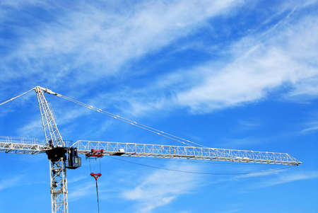 Tall construction crane on background of deep blue sky