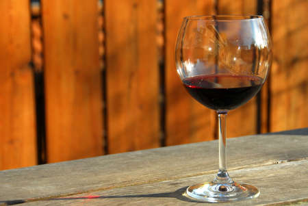 horisontal: Glass of red wine on old rustic table, horisontal