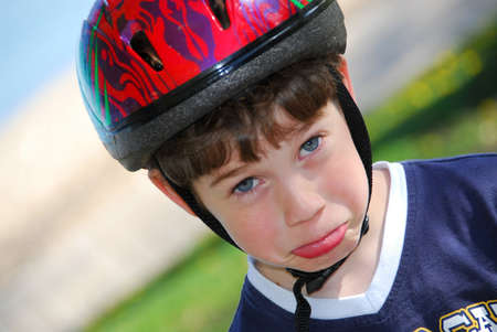 goofing: Portrait of a cute little boy in bicycle helmet making faces Stock Photo