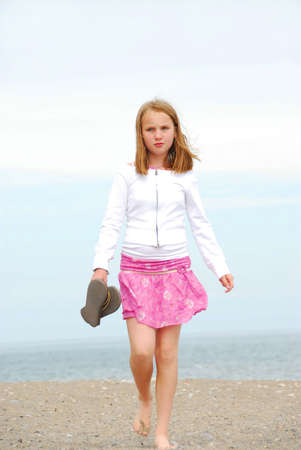 Young preteen girl walking on a sandy beach Stock Photo