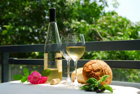Table setting with chilled white wine and glasses alfresco Standard-Bild