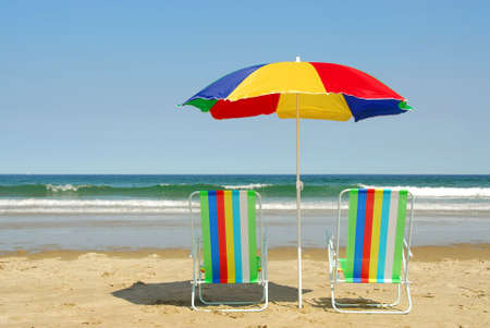 folding chair: Beach chairs and umbrella on the ocean shore with surf in the background, horisontal Stock Photo