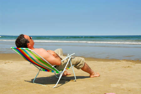 Man relaxing in a beach chair on the ocean shore