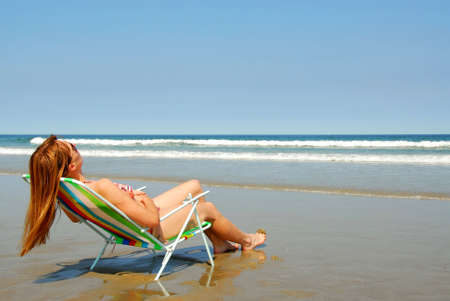 folding chair: Young woman relaxing in a beach chair on the ocean shore