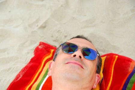 Man in sunglasses relaxing on beach, sunglasses reflect beach umbrella above. photo