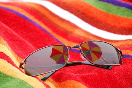 Sunglasses on beach towel relfecting beach umbrella above them photo