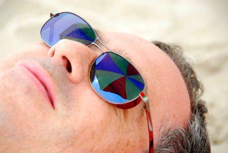 Man relaxing on a beach, focus on umbrella reflections in mans sunglasses photo