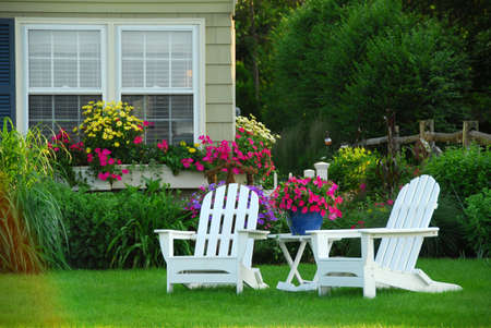 Two lawn chairs in a beautifl garden photo