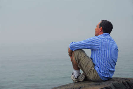 unclear: Man sitting on a rocky shore, looking at the foggy ocean. Uncertain future concept