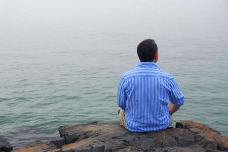 lean back: Man looking at the foggy ocean. Uncertain future concept.