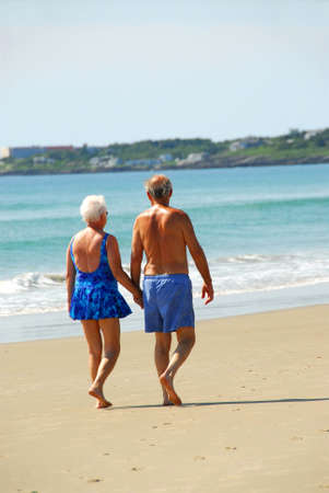Happy retired couple taking a walk on a beach holding hands photo