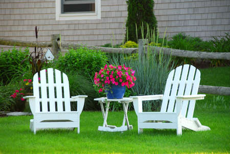 adirondack chair: Two lawn chairs in a beautifl garden near cottage