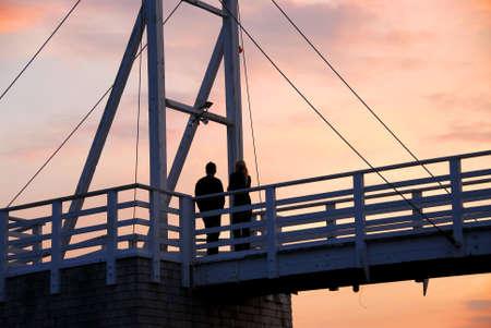 vlonder: Paar zonsondergang kijken op een loopbrug in Perkins Cove, Maine