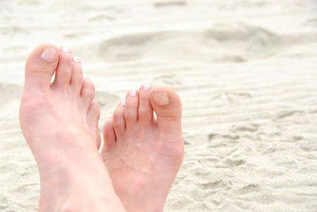 u�as pintadas: Cruz� los pies de arena en la playa  Foto de archivo