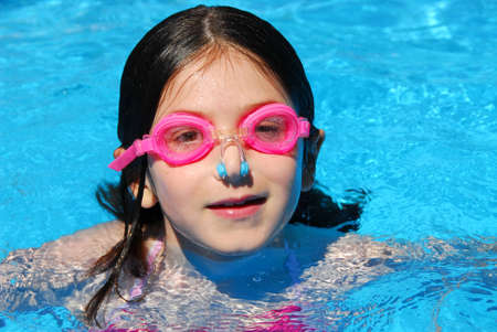 Portrait of a smiling girl in pink goggles in a swimming pool photo