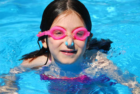 pool preteen: Portrait of a smiling girl in pink goggles in a swimming pool