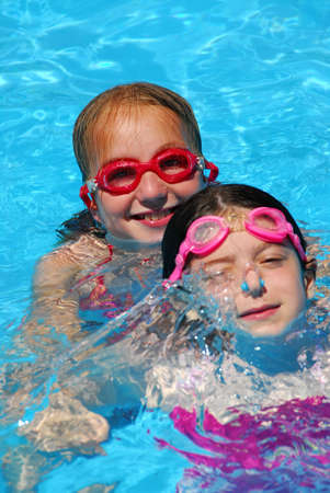 Two young girls having fun in a swimming pool photo