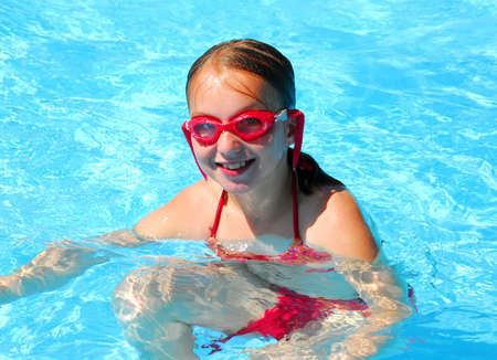 Girl in red goggles in swimming pool photo