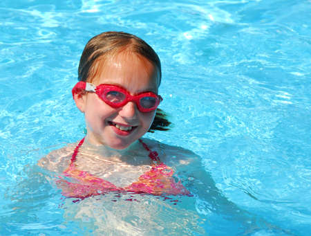 pool preteen: Young girl in red goggles in swimming pool Stock Photo