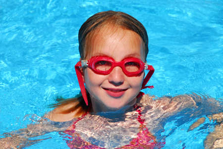 Young girl in red goggles in a swimming pool photo