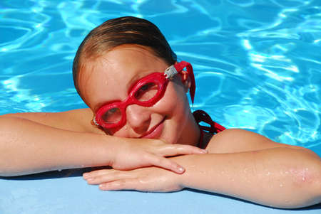 Portrait of a young girl in red goggles resting at the pool edge photo