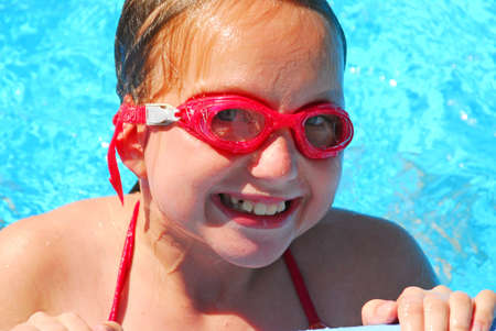 Portrait of a smiling girl in red goggles resting at the pool edge photo