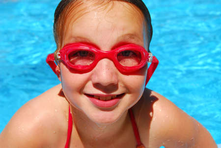 Portrait of a smiling girl in red goggles photo