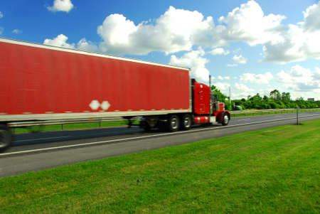 moving truck: Fast moving truck with red container on highway, blurred because of fast motion Stock Photo