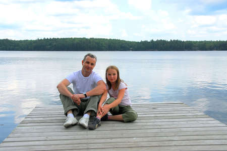 Father and child sitting on a wooden pier on a lake