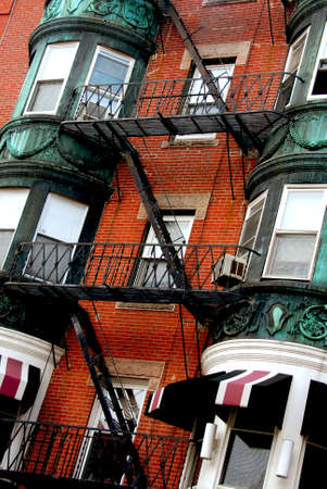 Fragment of a red brick house in Boston historical North End with wrought iron balconies and fire escapes photo