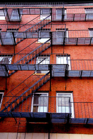 Fragment of a red brick house in Boston historical North End with iron fire escapes and balconies photo