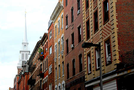Steeple of Old North Church in Boston North End, row of historical brick buildings in foreground photo