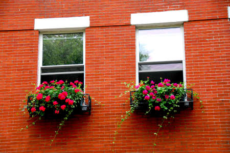 Fragment of a red brick house in Boston historical North End with wrought iron flower boxes