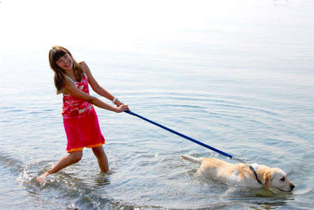 Happy girl playing with her dog in water photo