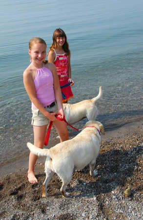 preteens beach: Two girls playing with dogs on a beach