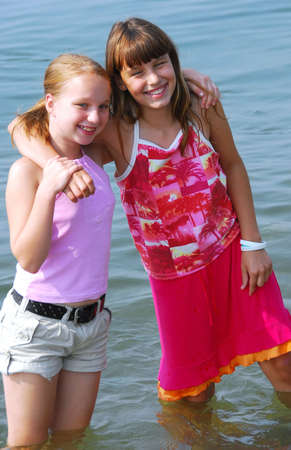 Portrait of two preteen girls standing in water