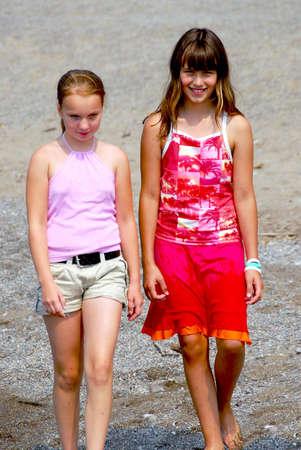 Two preteen girls walking on a beach photo
