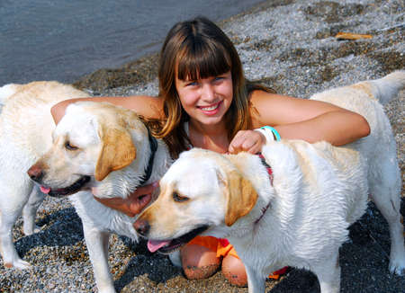 Portrait of a young pretty girl with two dogs on a beach photo