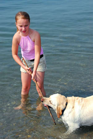 Young pretty girl playing with a dog in lake water